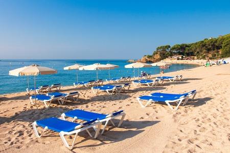 Cala de Fenals beach in Lloret de Mar, Costa Brava. Sandy resort beach in Spain with deck chairs and sun umbrellas