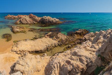 Rock on sandy sea resort beach in Costa Brava, Lloret de Mar. Summer amazing seascape on clear day in Spain