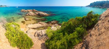Spain beach. Costa brava resort beach. Rocks in sandy beach Cala Treumal and Santa Cristina in Lloret de Mar. Sunny day in spanish coast