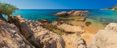 Panorama Lloret de mar sea beach on sunny clear day. Blue lagoon in Costa Brava with rocks on sand beach Cala Treumal