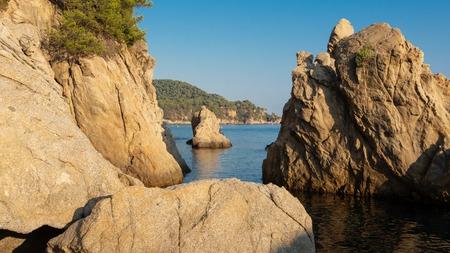 Rocks on Cala de Boadella beach in Lloret de Mar. Scenic sea nature landscape. Cliffs in sea shore in Costa Brava, Spain. Spanish coast in clear morning