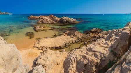 Santa Cristina beach in Lloret de Mar, Costa Brava, Spain on sunny clear day. Blue seascape with rocks on sandy beach in Spain Imagens