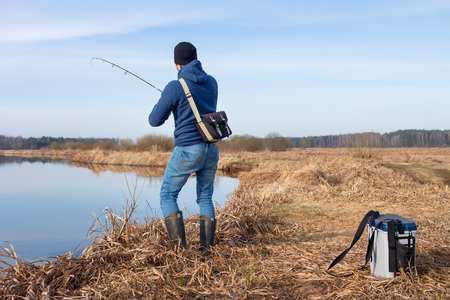 Fisherman catches fish in river at springtime. Man with spinning on fishing
