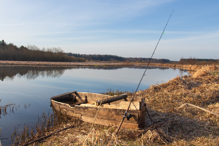 Rural landscape with boat and fishing rod on river side at spring. Fishing in spring