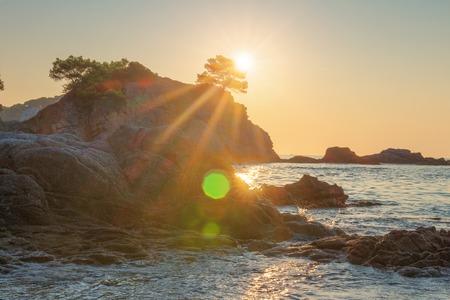 Bright sunrise on sea beach in Lloret de Mar. Sun shine over rocky cliff in Costa Brava beach. Spanish coast in morning sunlight.