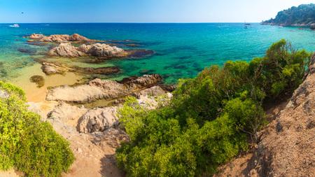 Lloret de Mar beach. Spain resort beach on sunny clear day. Sandy beach on summer vacation in spanish coast. Costa Brava nature landscape.
