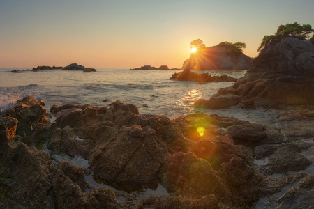 Sea rocky beach landscape at sunrise. Sun shine on spanish coast Costa Brava in Lloret de Mar, Spain