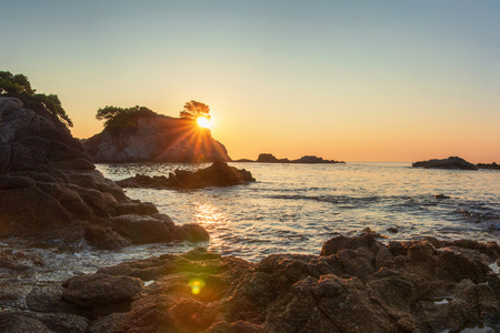Bright sunrise at sea coast in Costa Brava, Spain. Beautiful sea rocky beach in sun shine Stok Fotoğraf