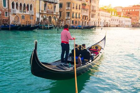 Venetian gondolier carries tourists on gondola Grand Canal of Venice, Italy Stok Fotoğraf