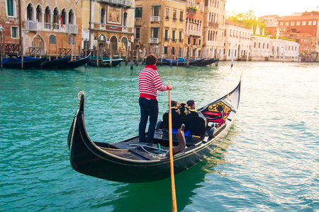 Venetian gondolier carries tourists on gondola Grand Canal of Venice, Italy Standard-Bild