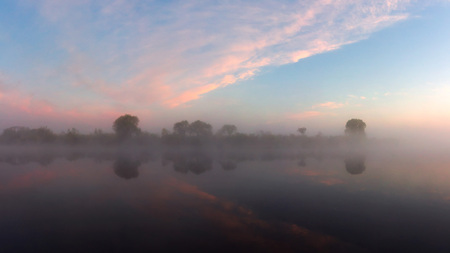 Summer river in morning dawn. Nature landscape on river with reflections of sky in water Imagens