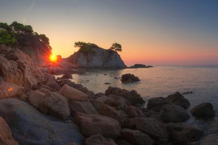 Bright sunrise in Lloret de Mar. Spain nature landscape in the morning. Sun shines through cliff on sea beach in Costa Brava. Scenic  dawn Cala de Fenals beach