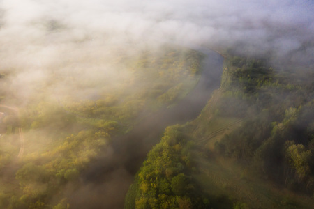 Beautiful foggy morning landscape of river view from above. Aerial view of clouds over wild river nature