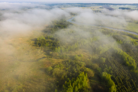 Foggy summer morning nature aerial view. Mist over green meadow with river. Misty nature landscape from above