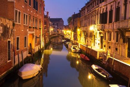 Venice night cityscape with boats in canal, Italy. Venice street illuminated night lanterns.