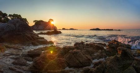 Scenic view on spanish sea coast in lloret de mar at sunrise. Costa Brava rocky beach in sun shine