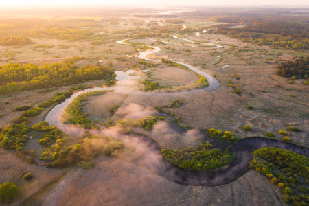 Summer background at sunrise. Aerial nature background. Foggy river view from above. Bright morning landscape drone view