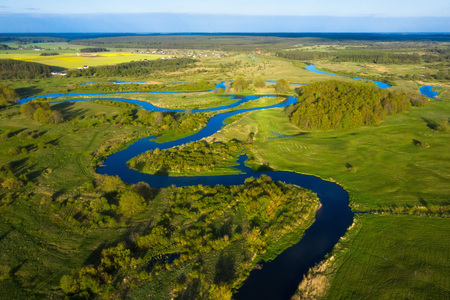 Curved river on green meadow top view. Aerial view of river nature on sunny day. River landscape