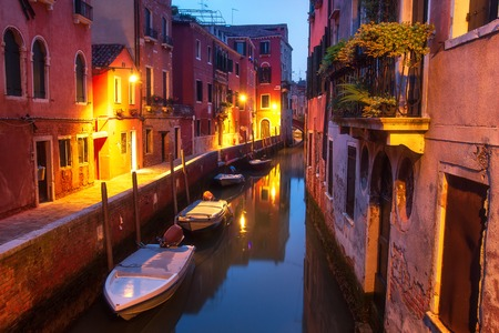 Beautiful night cityscape of Venice, Italy. Boats and houses on water canal illuminated lights of city lanterns