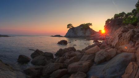 Sunrise on Costa Brava coast. Spanish sea landscape. Morning dawn on sea beach with rocks and cliffs. Standard-Bild