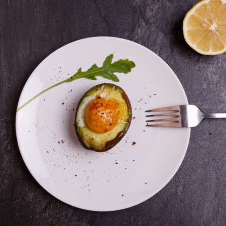 Cooked avocado with egg on a white plate on a dark background. On the plate lies a fork, near the lemon