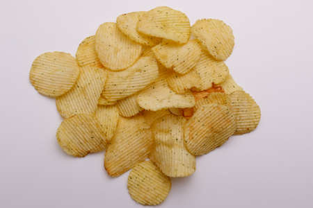 Closeup image of potato chips on a white background