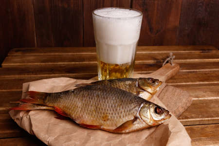 Close-up dried fish, a glass of beer on a dark wooden background.