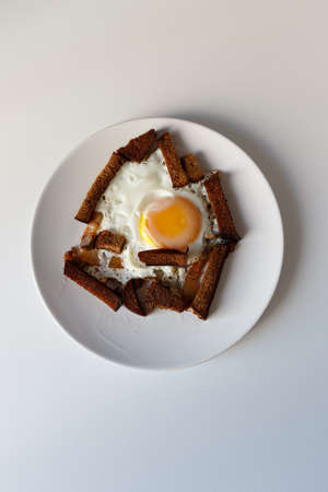 fried egg, bread and lard on a white plate, on a white background