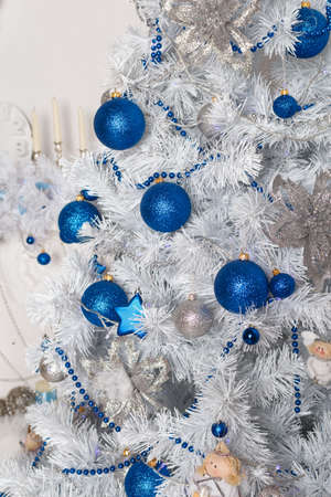 Blue and silver Christmas balls and stars on the branches of a white Christmas tree