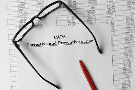 CAPA corrective and preventive action plans paper. Document on the table