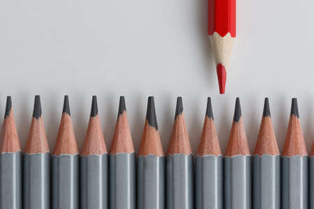 Support Group, Intervention. Conceptual. Red and gray pencils opposite each other on an isolated background. Shallow depth of field