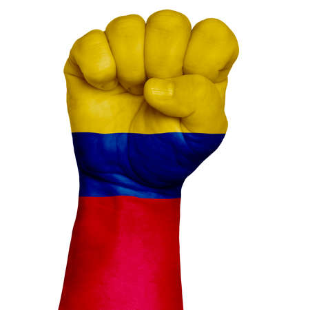 Low key picture of a fist painted in colors of colombia flag. Image on a white background. Isolate
