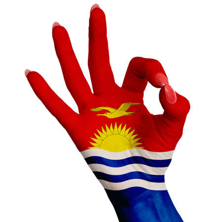 The national flag of Kiribati is painted on a female hand showing the OK sign. Image on a white background