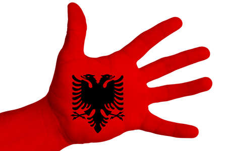 The national flag of Albania is painted on a male hand. Image on a white background. Isolate