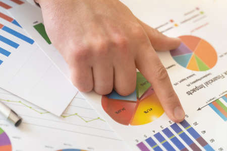 Close up Businessman hand holding pen and pointing at financial paperwork with financial network diagram. Financial concept