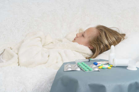 Sick teenage girl lies on the bed next to lying medication. Medical concept. 版權商用圖片