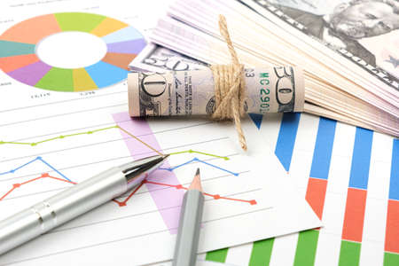 Business goal concept. Business accessory, graph charts and pencil and dollars on the table.