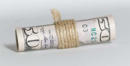 Dollars twisted into a roll isolated on a white background. Close-up