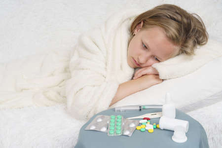 A sick teenage girl lies on the bed and looks at the medicine. Medical concept. 版權商用圖片