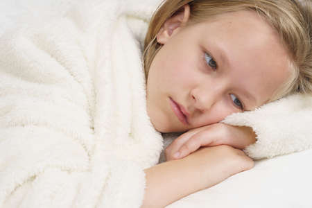 Sick teenage girl lies on the bed and looks away. Medical concept.