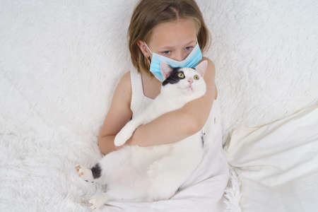 Sick teenage girl in a protective mask hugs a cat. Medical concept.