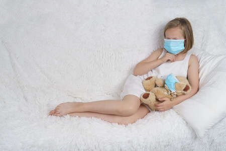 A sick teenage girl is playing with a toy wearing a protective mask. Medical concept.