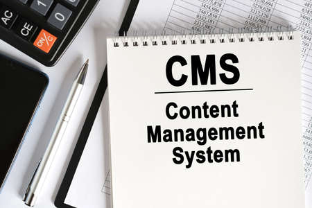 On the table lies a smartphone, a calculator and a notebook with the inscription - CMS. Content management system. Business concept
