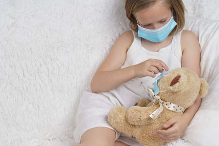 Sick teenage girl puts on a medical protective mask for a toy. Medical concept.