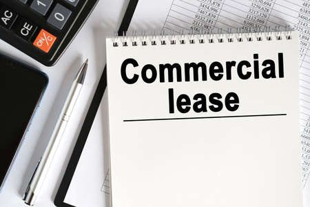 On the table lies a smartphone, a calculator and a notebook with the inscription- Commercial lease. Business concept