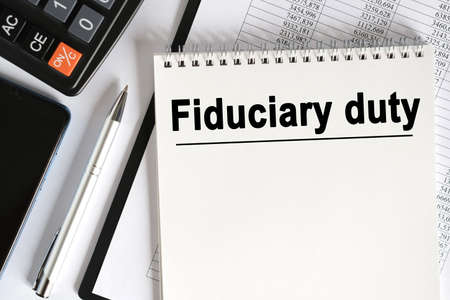 On the table lies a smartphone, a calculator and a notebook with the inscription- Fiduciary duty. Business concept