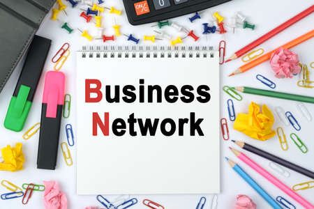 Business concept. On the table is a calculator, diary, markers, pencils and a notebook with the inscription - Business Network