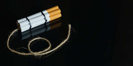The concept of medicine is the fight against smoking. Cigarettes are twisted into a dynamite checker with a filament on a black reflective surface.