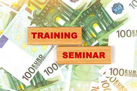Business concept. Against the background of euro bills, the text is written on wooden blocks - training seminar Imagens