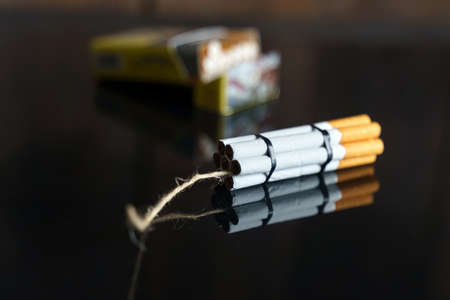 The concept of medicine is the fight against smoking. Cigarettes in the form of dynamite checkers on a black reflective surface, in the background a pack of cigarettes.